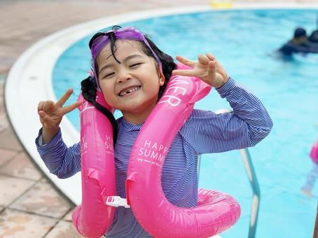 Peace girl with a smile by the pool