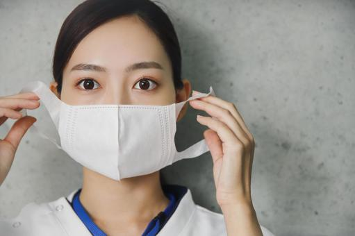Medical worker woman wearing a mask with a serious expression
