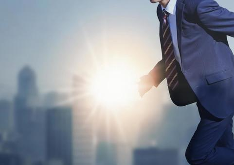 Running businessman and the light of dawn