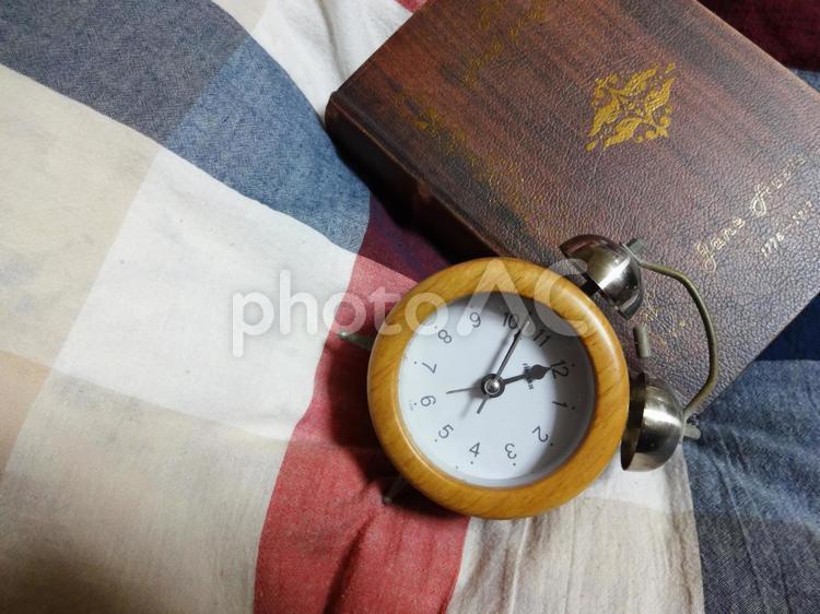 目覚まし時計と本の写真
