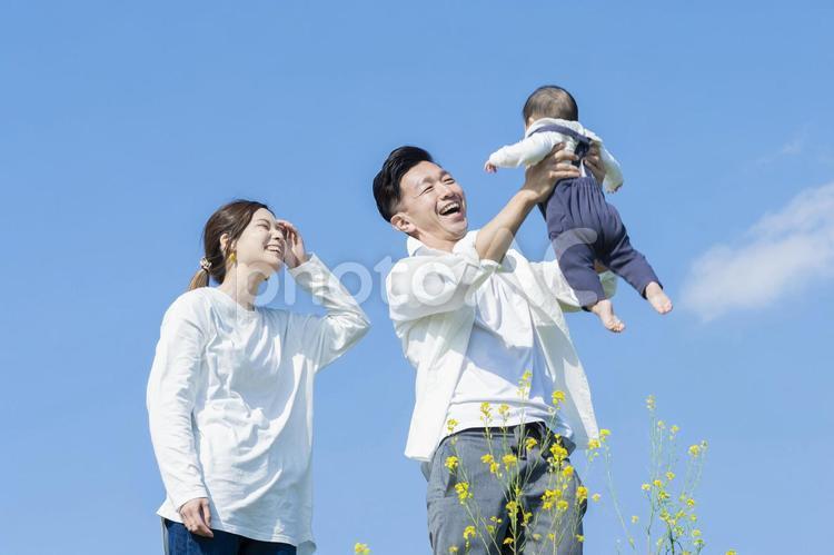 青空のもと、赤ちゃんを高く抱き上げる父母の写真