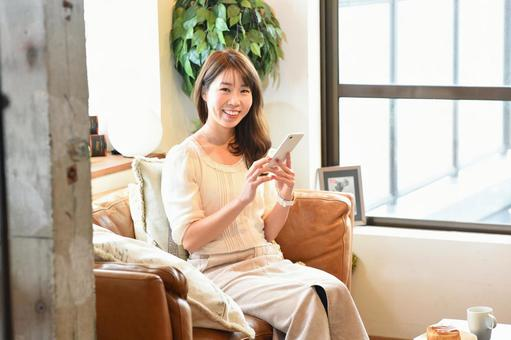 A smiling woman operating a smartphone