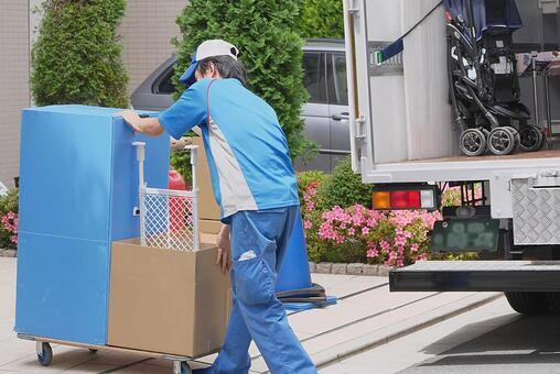 荷台で荷物を運ぶ引越しスタッフ