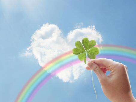 하트 모양의 구름과 푸른 하늘과 무지개 네잎 클로버를 가진 손