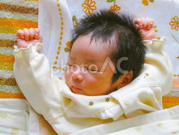 人物 子供 健康 ー 万歳しながら眠る赤ちゃん 男の子の写真