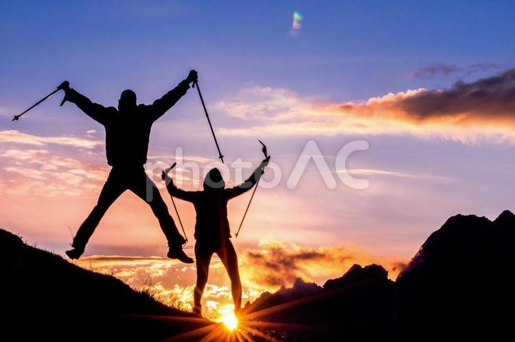 トレッキングをする男女のシルエットと朝日3の写真