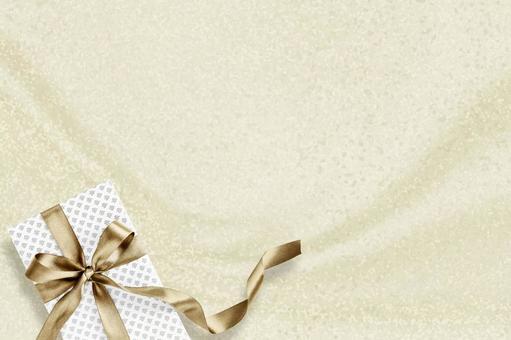 샴페인 골드 새틴 직물 배경에 금색 리본으로 묶인 선물