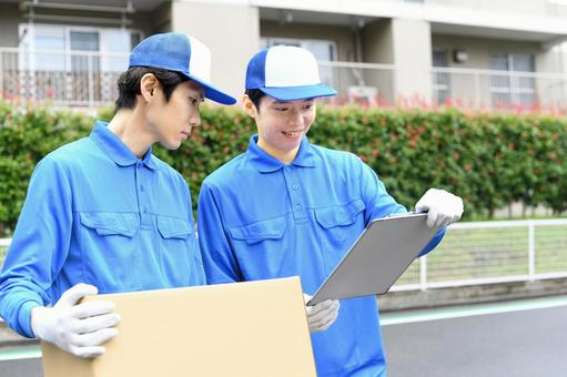 Image of multiple men wearing work clothes carrying moving cardboard outdoors