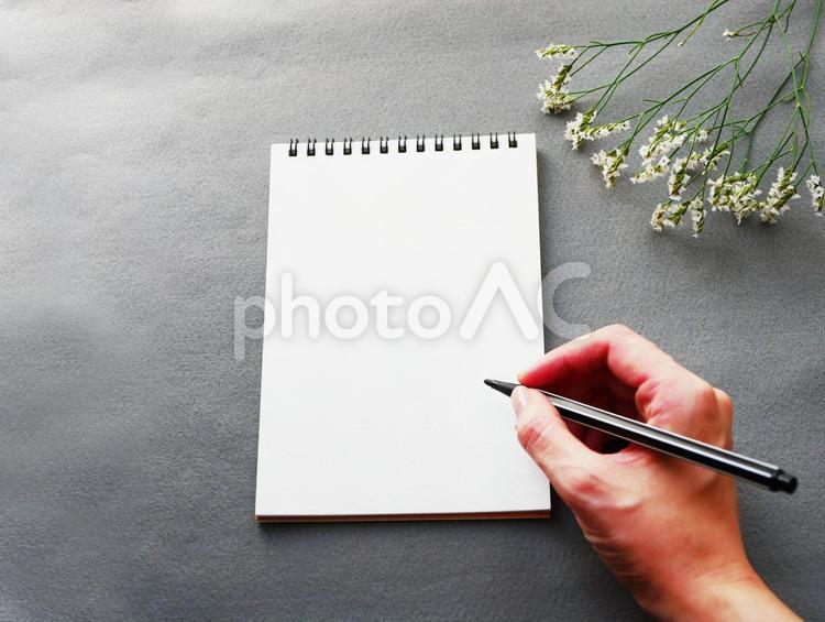 メモにペンで書くところ お花とグレー背景の写真