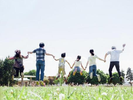 A three-generation family jumping hand in hand in a sunny park