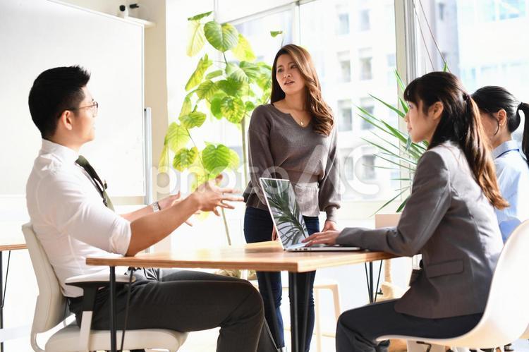 オフィスで会議をする笑顔の男性と女性のビジネスマンの写真