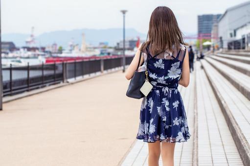 Back view of a woman walking along the coastal promenade
