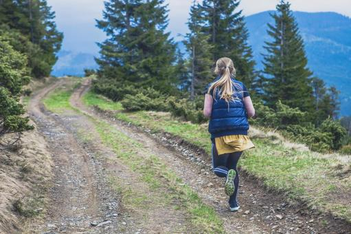 A woman running on a mountain path 6