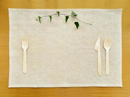 Wooden cutlery on both sides, ivy leaves and a natural placemat