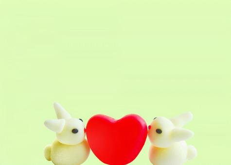 Two sideways rabbits and a red heart yellow-green background copy space