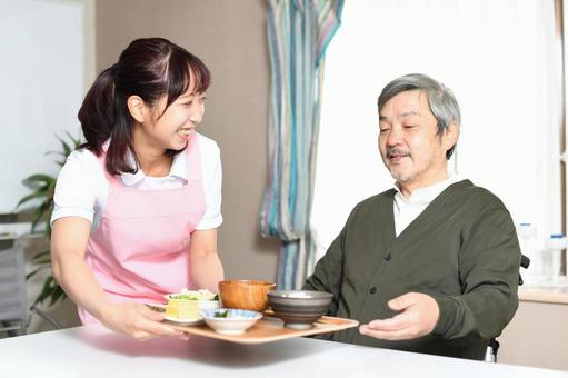 Female caregiver carrying food and elderly gray-haired man