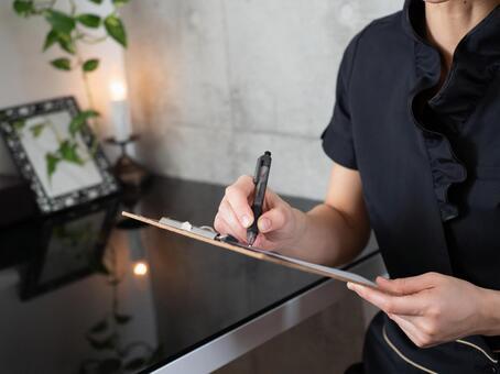 에스테틱 살롱에서 진료 기록 카드를 작성하는 검은 제복을 입은 미용사