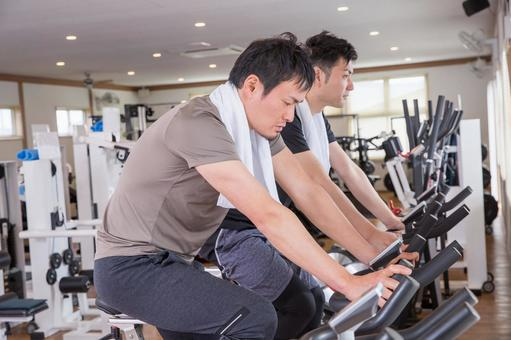A man riding a bicycle in a sports gym