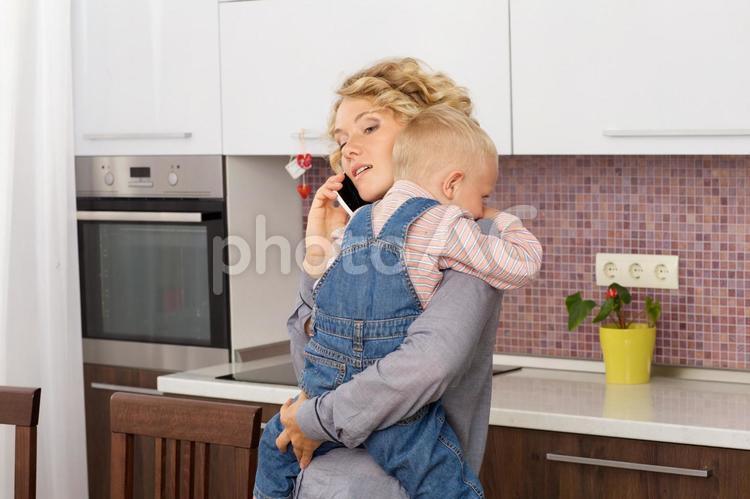 キッチンで息子を抱っこしながら電話をするお母さん3の写真