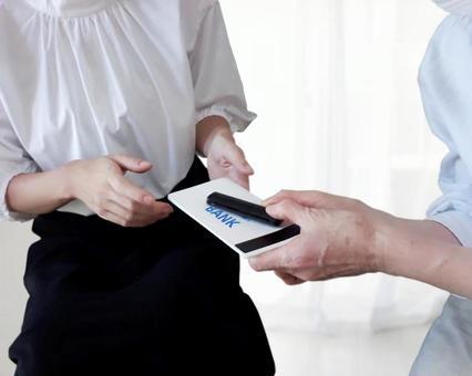 통장과 도장을 전달하는 여성과 노인
