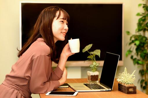 A young woman operating a laptop while relaxing