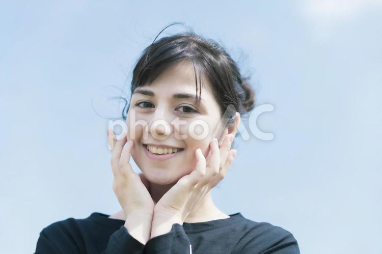 青空と笑顔の女性の写真
