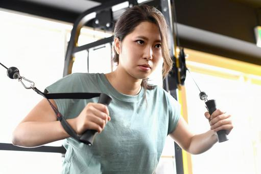 Young woman doing muscle training (cable press down) at the gym