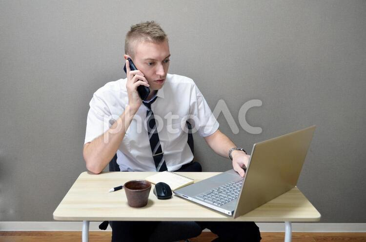 電話で話しながらパソコンをしている会社員男性の写真