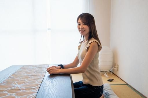 A smiling woman sitting in a Japanese-style room