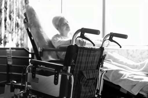 An elderly woman with dementia and a wheelchair playing with towelettes while relaxing in a nursing bed