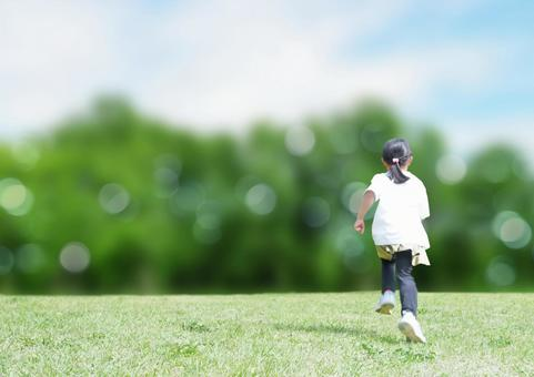 Running child back view green background
