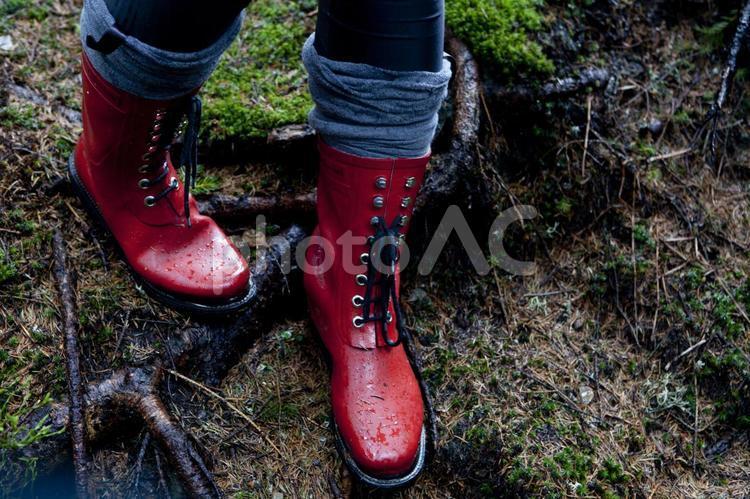沢を歩く赤い長靴の女性の足元1の写真