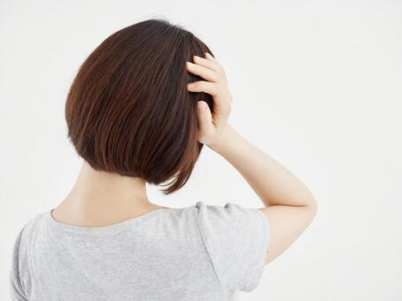 A woman holding her head aching on a white background