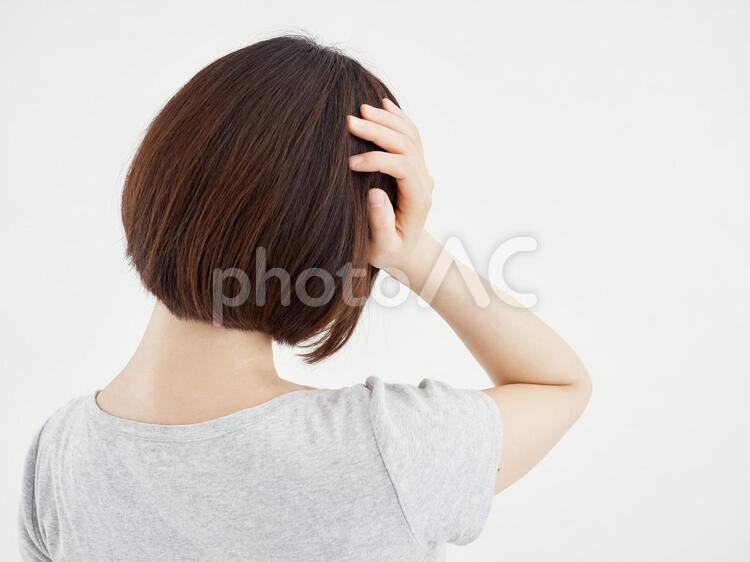 白背景で痛む頭を抑える女性の写真