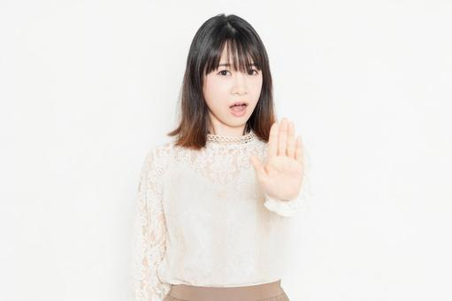 Young woman in lace blouse standing in front of white background and making NG gestures