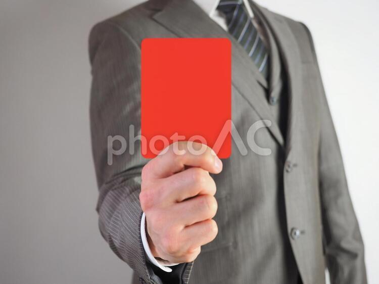 レッドカードを出すビジネスマンの写真