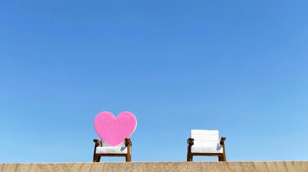There is a small distance of 2 chairs and 1 heart _ blue sky