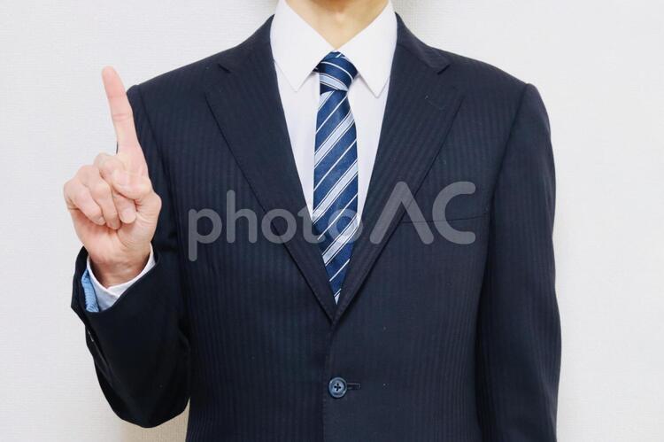 人差し指を立てるスーツの男性の写真
