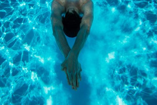 The upper body of a swimming man seen from above