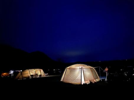 Lights of two tents in the campsite at night