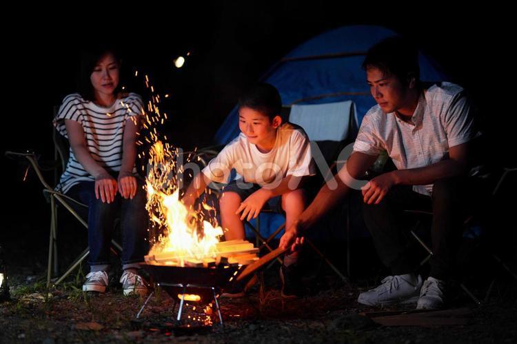キャンプで焚き火をする親子の写真