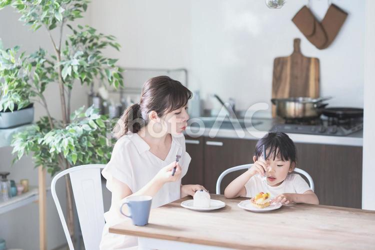 部屋でケーキを食べる親子の写真