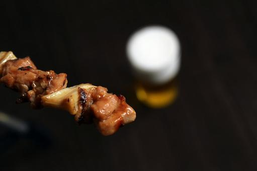 Beer and yakitori on a wooden table