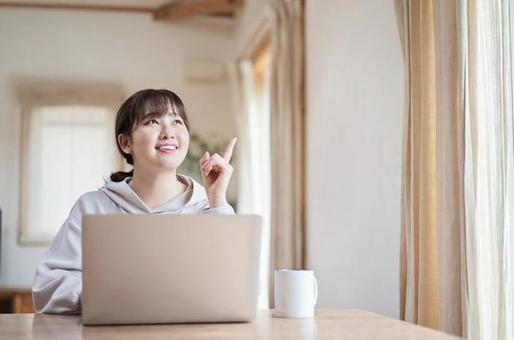 거실에서 웃는 얼굴로 컴퓨터 작업을하는 아시아 여성