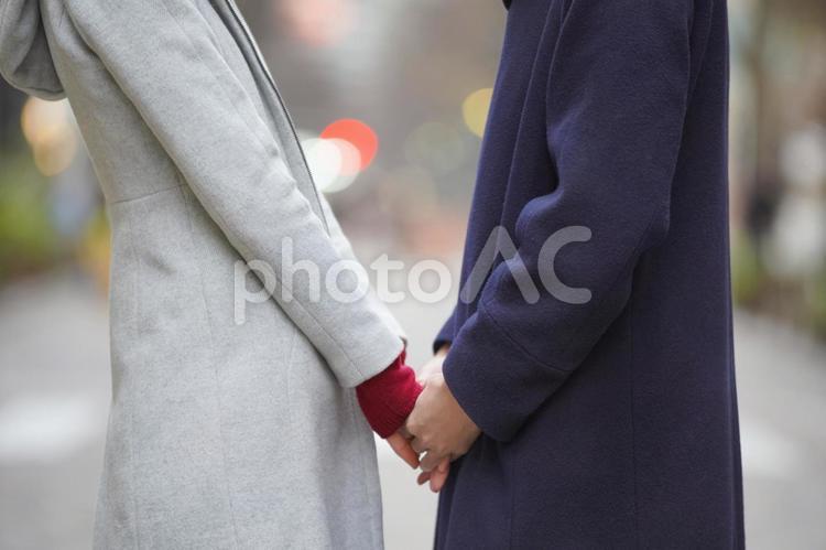 手を繋ぎ見つめ合うカップルの写真
