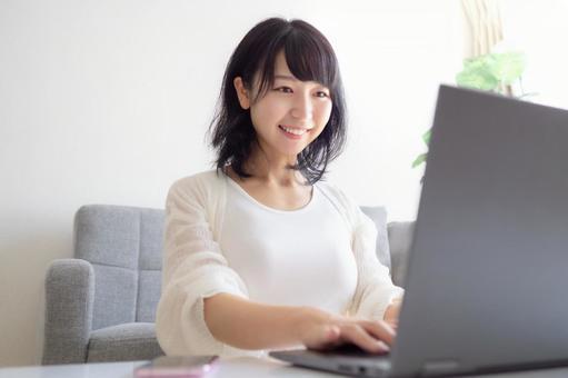 스마트 폰과 PC를 조작하는 젊은 여성의 이미지