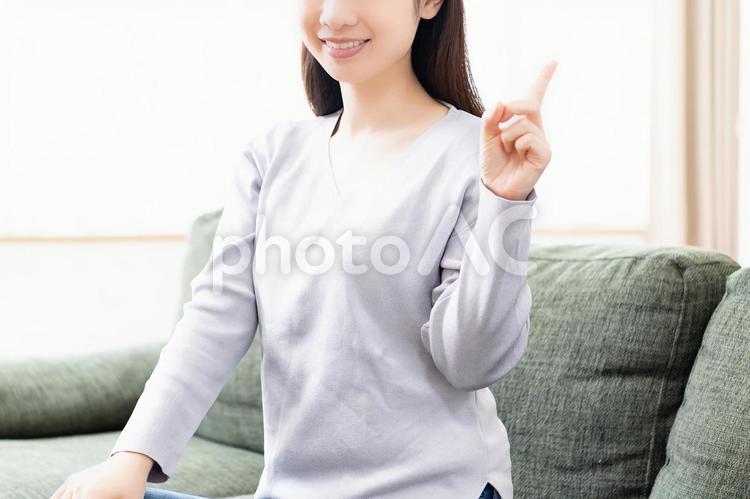 人差し指でポイントを示す若い女性の写真