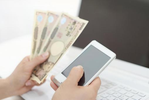 A woman with a smartphone and a 10,000 yen note