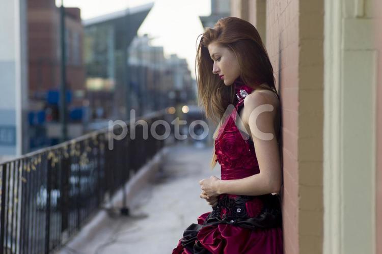 壁に寄りかかる赤いドレスの女性2の写真