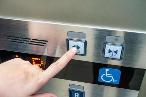 A photo of a person pushing an elevator button.